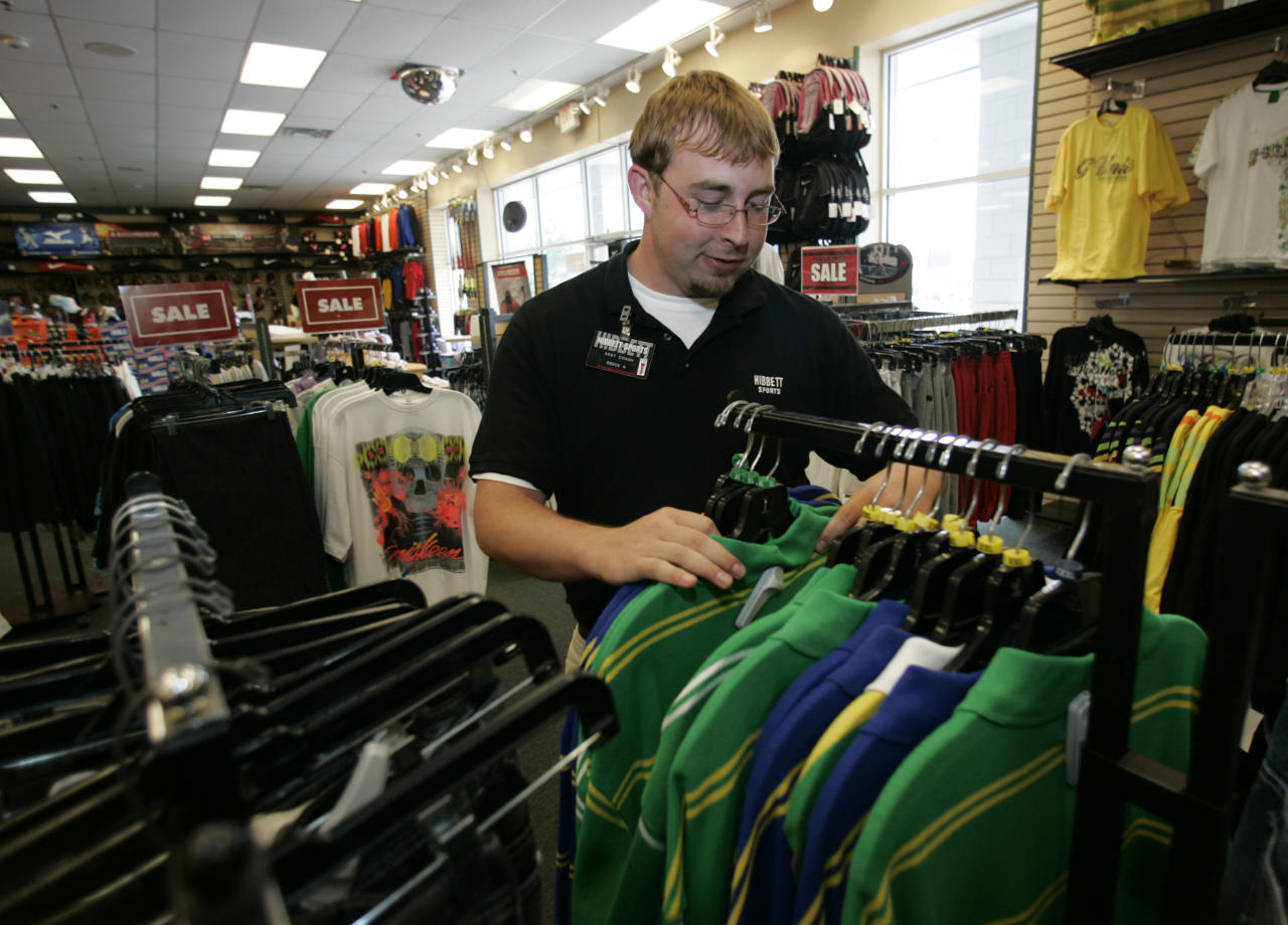 "FILE - In this Wednesday, June 25, 2008, file photo, Reece Armistead, an assistant manager at Hibbett Sports in Thomasville, Ala., sorts clothing at the store. Hibbett, a chain with more than 1,000 stores, said it expects a key sales figure to fall due to a ""challenging"" retail environment. Hibbett's stock fell Monday, July 24, 2017, after the announcement. And shares of its competitors, such as Foot Locker and Dick's Sporting Goods, also fell. (AP Photo/Dave Martin, File)"