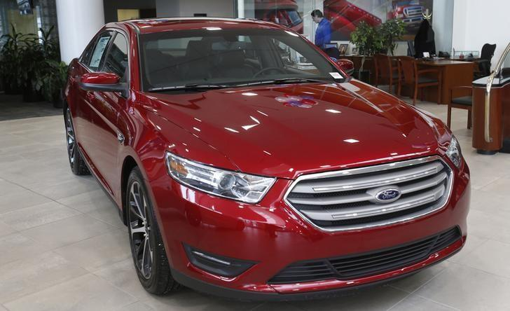 A 2015 red Ford Taurus sedan is seen in the showroom at the Suburban Ford dealership in Sterling Heights, Michigan