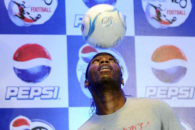 International football player from Ivory Coast, Didier Drogba heads a football during a press conference at a function in New Delhi on June 17, 2012.  Didier Drogba is in the city for the grand finale of the Pepsi T20 football tournament.   AFP PHOTO/ SAJJAD HUSSAIN