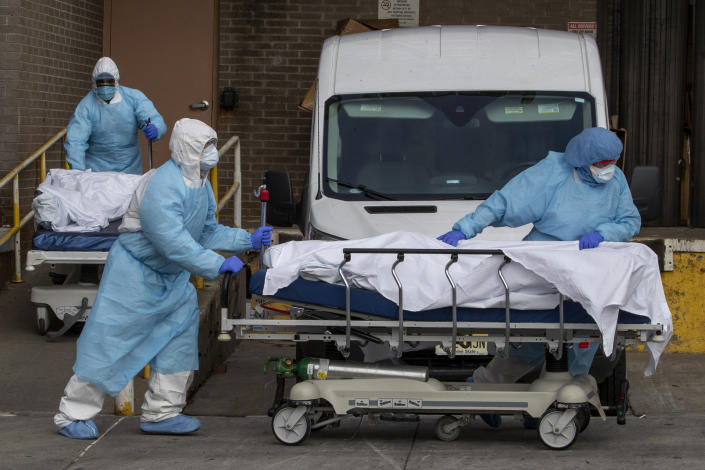 Medical personnel remove bodies from a hospital in Brooklyn Thursday. (Mary Altaffer/AP)