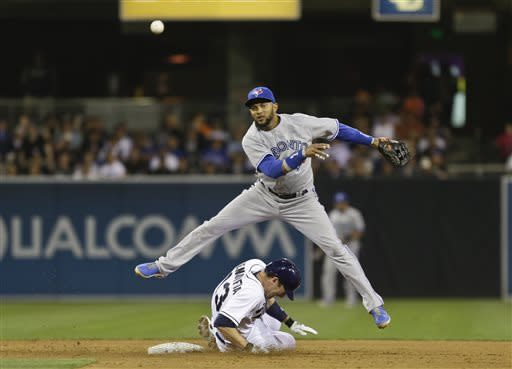 Toronto Blue Jays second baseman Emilio Bonifacio leaps over San Diego Padres' Chris Denorfia while relaying to first on an unsuccessful attempt for a double play in the sixth inning of a baseball game in San Diego, Friday, May 31, 2013. (AP Photo/Lenny Ignelzi)