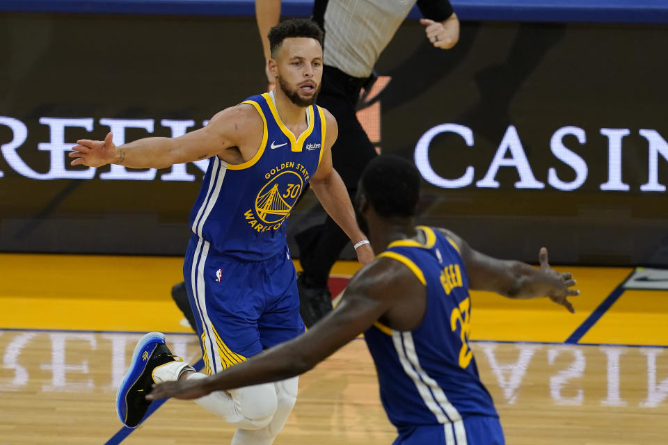 Golden State Warriors guard Stephen Curry, top, celebrates with forward Draymond Green during the second half of an NBA basketball game against the Cleveland Cavaliers in San Francisco, Monday, Feb. 15, 2021. (AP Photo/Jeff Chiu)