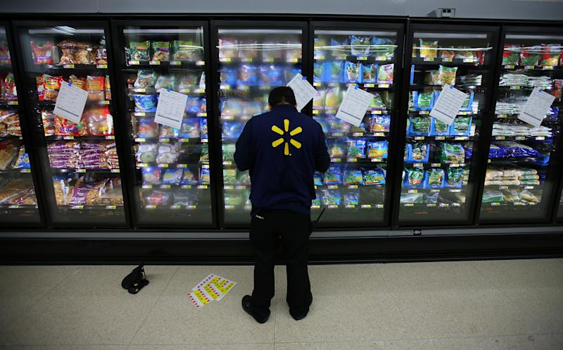 A worker prepares the frozen food section at a newly built Walmart Super Center prior to its opening in Compton, California, U.S., January 10, 2017. REUTERS/Mike Blake