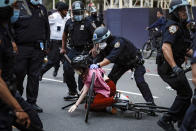 FILE — In this June 3, 2020 file photo, a protester is arrested by NYPD officers for violating curfew beside New York's iconic Plaza Hotel, following the death of George Floyd, who died after being restrained by Minneapolis police officers. The New York Police Department was caught off guard by the size and scope of the spring protests sparked by the police killing of George Floyd in Minneapolis and resorted to disorder control tactics that stoked tensions and stifled free speech rights, the city's inspector general said in a report released Friday, Dec. 18, 2020.(AP Photo/John Minchillo, File)