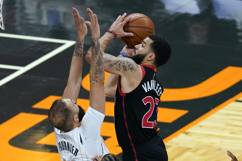Toronto Raptors guard Fred VanVleet, right, goes up against Orlando Magic guard Evan Fournier for a shot during the second half of an NBA basketball game, Tuesday, Feb. 2, 2021, in Orlando, Fla. (AP Photo/John Raoux)