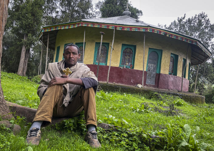 """Priest Yared Adamu holds an Ethiopian Orthodox cross in the churchyard where residents say more than 50 civilians have been laid to rest in makeshift graves, in the village of Chenna Teklehaymanot in the Amhara region of northern Ethiopia Thursday, Sept. 9, 2021. At the scene of one of the deadliest battles of Ethiopia's 10-month Tigray conflict, witness accounts reflected the blurring line between combatant and civilian after the federal government urged all capable citizens to stop Tigray forces """"once and for all."""" (AP Photo)"""