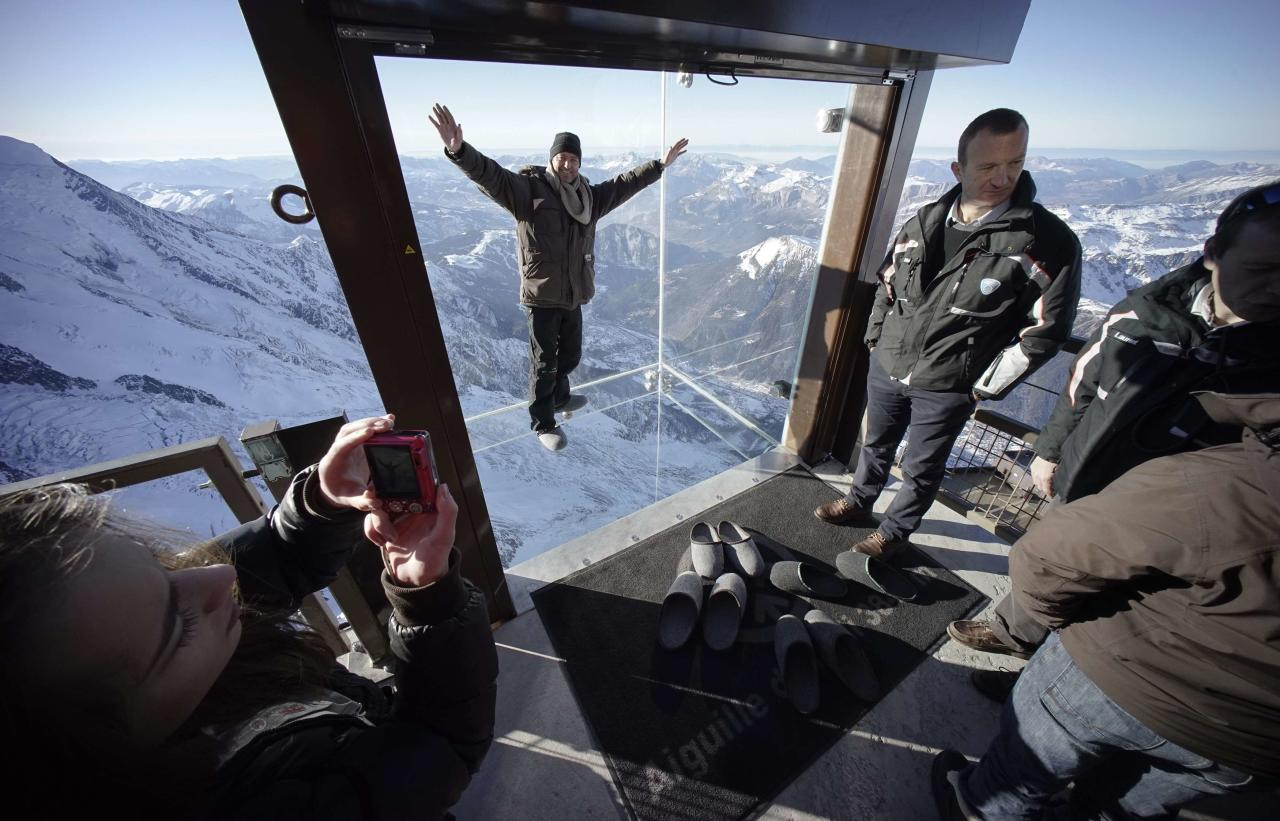 Journalists and employees, wearing slippers to protect the glass floor, visit the 'Step into the Void' installation as they attend a press visit at the Aiguille du Midi mountain peak above Chamonix, in the French Alps, December 17, 2013. The Chamonix Skywalk is a five-sided glass structure installed on the top terrace of the Aiguille du Midi (3842m), with a 1,000 metre drop below, where visitors can step out from the terrace, giving the visitors the impression of standing in the void. The glass room will open to the public on December 21, 2013. REUTERS/Robert Pratta (FRANCE - Tags: SOCIETY TRAVEL CITYSCAPE)