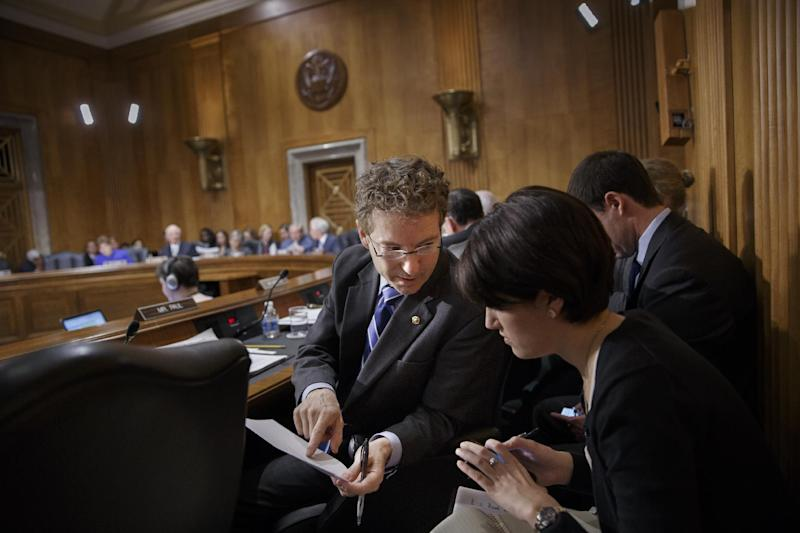 Sen. Rand Paul, R-Ky., confers with an aide as the Senate Foreign Relations Committee drafts legislation that would show support for the people of Ukraine and send a get-tough message to Russian President Vladimir Putin for taking over the Crimea region, on Capitol Hill in Washington, Wednesday, March 12, 2014. The committee was set to meet with acting Ukrainian Prime Minister Arseniy Yatseniuk later. (AP Photo/J. Scott Applewhite)