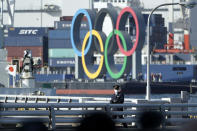 A police officer patrols near the Olympic Symbol being transported on a barge in the Odaiba section Tuesday, Dec. 1, 2020, in Tokyo. The five Olympic rings are back in Tokyo Bay. They were removed for maintenance four months ago shortly after the Tokyo Olympics were postponed until next year because of the COVID-19 pandemic. (AP Photo/Eugene Hoshiko)