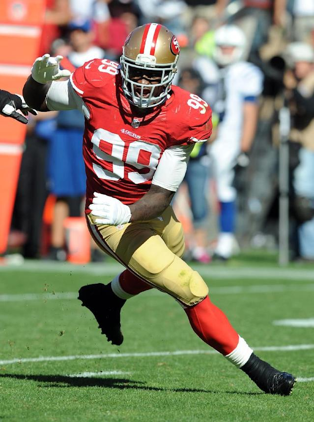 FILE - In this Sept. 22, 2013 file photo, San Francisco 49ers outside linebacker Aldon Smith (99) moves in on a play against the Indianapolis Colts at Candlestick Park in San Francisco. Two key faces have been absent as they seek new contracts, right guard Alex Boone and tight end Vernon Davis. On the defensive side, linebacker Aldon Smith and cornerback Chris Culliver each dealt with offseason arrests and court appearances. (AP Photo/John Cordes, File)