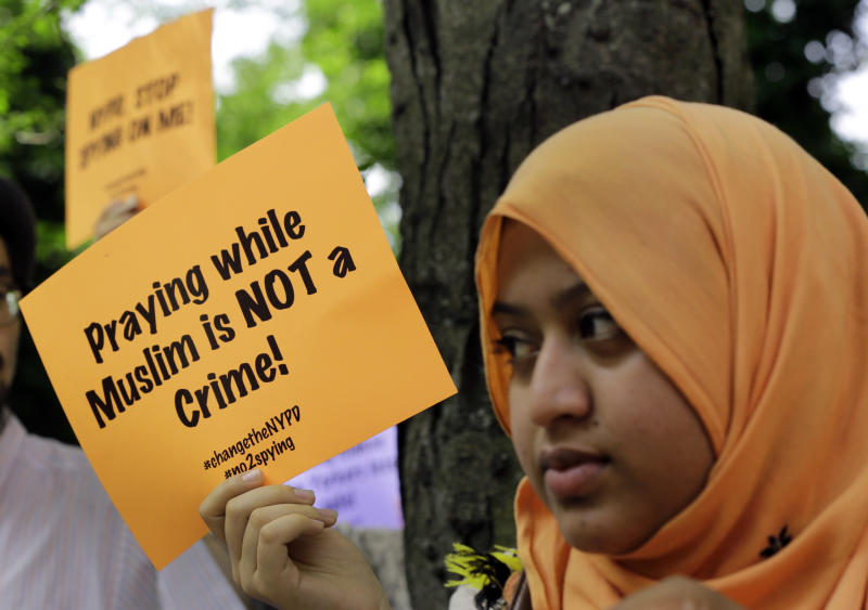 Supporters of a lawsuit challenging the NYPD's Muslim surveillance program, hold signs during a gathering on a plaza in front of New York City Police Department headquarters, Tuesday, June 18, 2013. In a lawsuit filed Tuesday, civil rights lawyers urged a U.S. judge to declare the NYPD's widespread spying programs directed at Muslims to be unconstitutional, order police to stop their surveillance and destroy any records in police files.(AP Photo/Richard Drew)