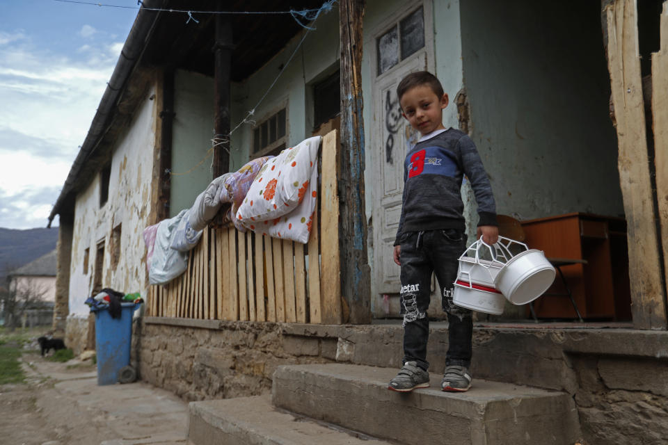 Milan Bastyur, a 4 year old Hungarian Roma child, holds containers as he goes to pick up food for lunch in Bodvaszilas, Hungary, Monday, April 12,2021. Many students from Hungary's Roma minority do not have access to computers or the internet and are struggling to keep up with online education during the pandemic. Surveys show that less than half of Roma families in Hungary have cable and mobile internet and 13% have no internet at all. (AP Photo/Laszlo Balogh)