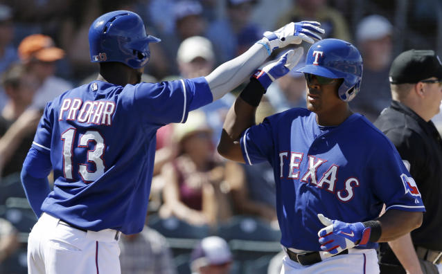 Texas Rangers' Adrian Beltre is congratulated by Jurickson Profar after scoring during the fourth inning of a spring exhibition baseball game against the Milwaukee Brewers Friday, March 21, 2014, in Surprise, Ariz. (AP Photo/Darron Cummings)