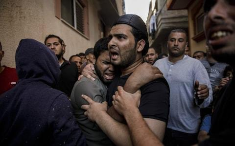 Relatives of Taher Ahmed Madi, 25, mourn his death after his body from the Shifa Hospital morgue arrives at his home after he was killed during a protest at the border fence separating Israel and Gaza on May 14  - Credit:  Marcus Yam/Los Angeles Times via Getty Images