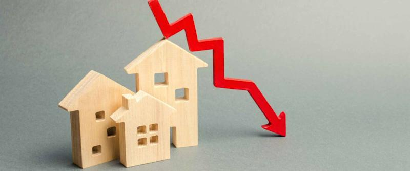 Miniature wooden houses and a red arrow down. The concept of falling mortgage rates.