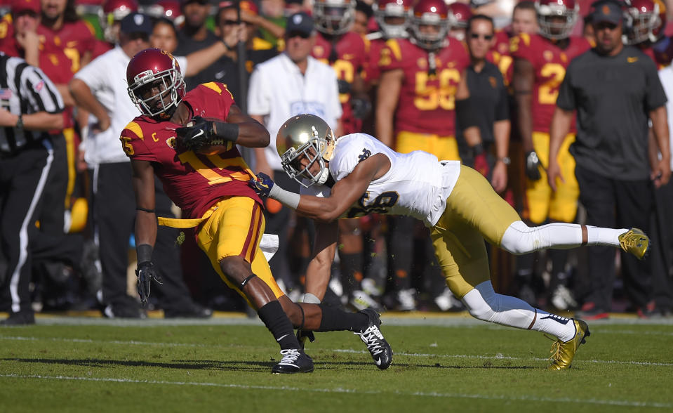 Southern California wide receiver Nelson Agholor is tackled by Notre Dame cornerback Cole Luke during the first half of an NCAA college football game, Saturday, Nov. 29, 2014, in Los Angeles. (AP Photo/Mark J. Terrill)