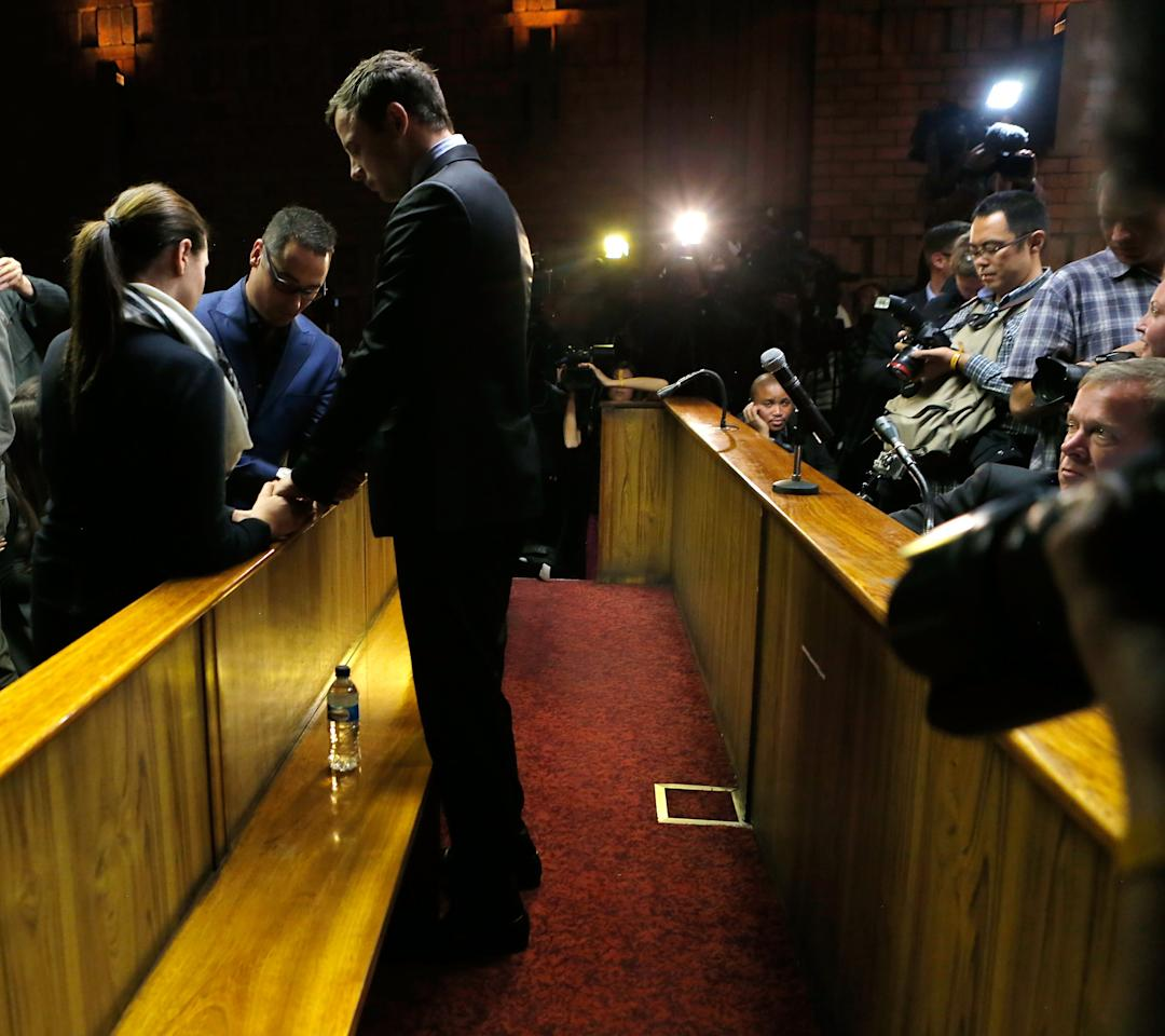 PRETORIA, SOUTH AFRICA - AUGUST 19: South African athlete Oscar Pistorius (C) prays with his brother Carl Pistorius and his sister Aimee Pistorius prior to his indictment hearing in Pretoria Magistrates Court on August 19, 2013. Pistorius, 26 is accused of murdering his girlfriend Reeva Steenkamp which Pistorius denies claiming he mistook Steenkamp for an intruder. The indictment was served and the trial date of March 3, 2014 has now been set. (Photo by Jemal Countess/Getty Images)