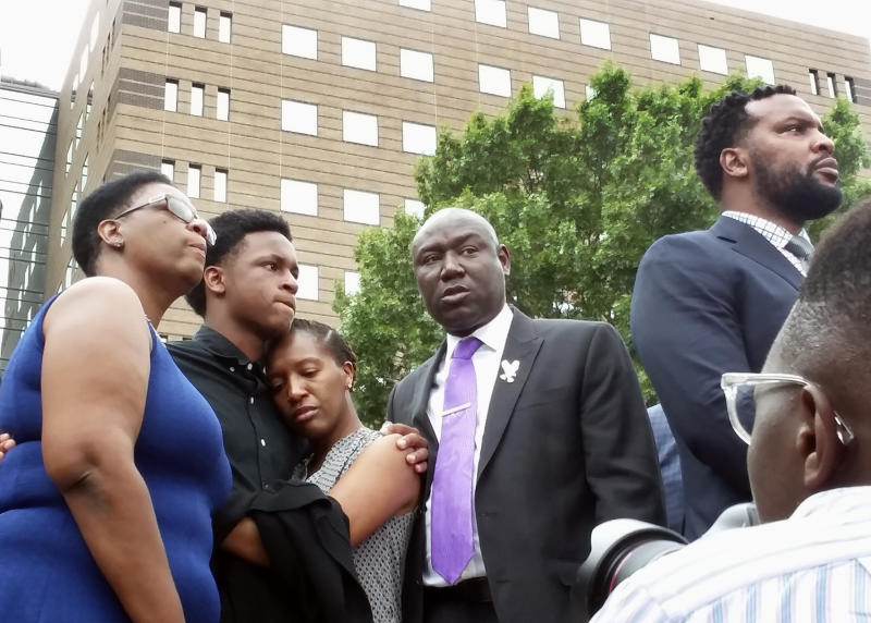 Allison Jean (far left), mother of Botham Shem Jean, stands alongside his brother and sister, as well as family attorneys Benjamin Crump and Lee Merritt, during a news conference on Sept. 10. (Ryan Tarinelli / AP)