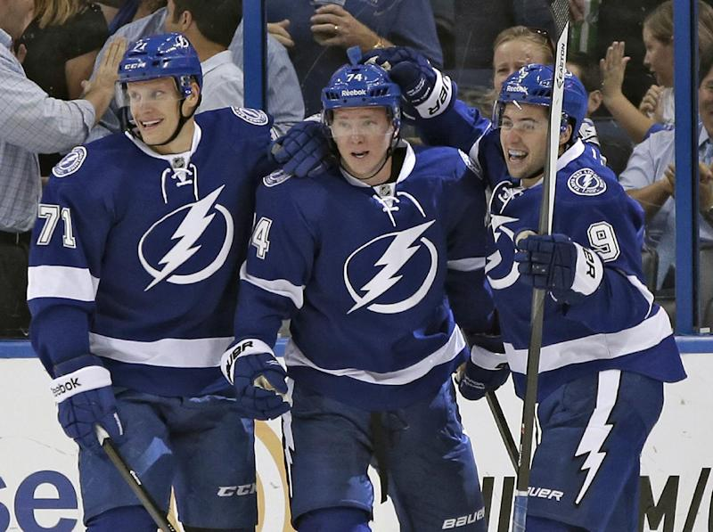 Tampa Bay Lightning left wing Ondrej Palat (74), of the Czech Republic, center, celebrates with teammates right wing Richard Panik (71), of Slovakia, left, and center Tyler Johnson, right, after scoring against the Nashville Predators during the first period of an NHL preseason hockey game Thursday, Sept. 19, 2013, in Tampa, Fla. (AP Photo/Chris O'Meara)
