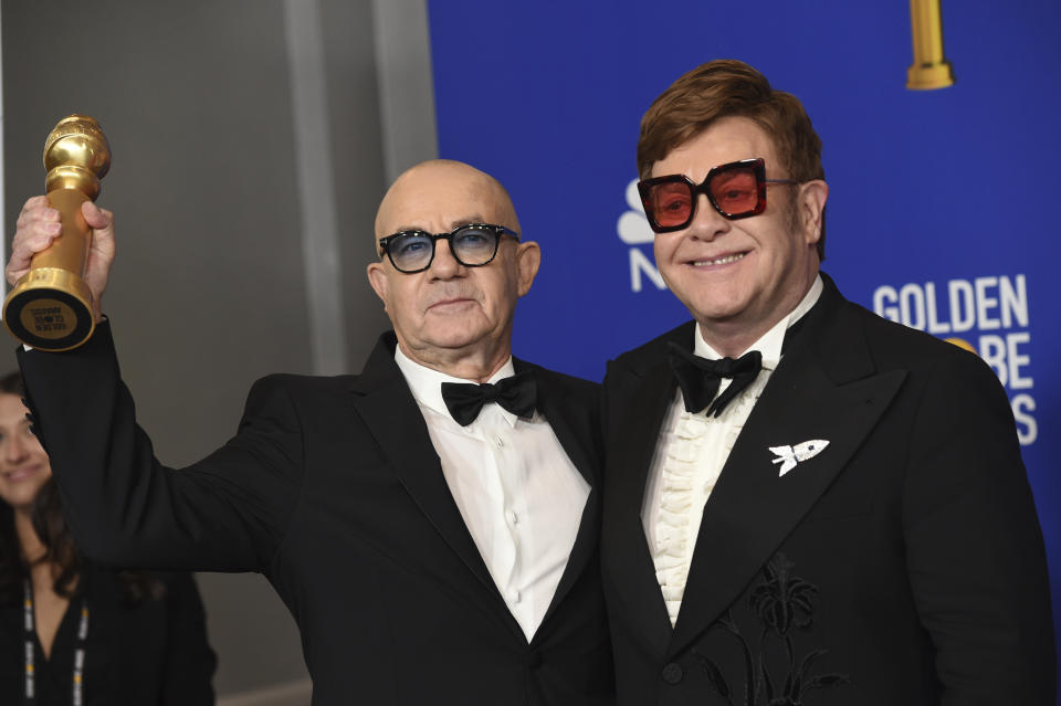 """Elton John, right, and Bernie Taupin pose in the press room with the award for best original score in a motion picture for """"I'm Gonna Love Me Again"""" from """"Rocketman"""" at the 77th annual Golden Globe Awards at the Beverly Hilton Hotel on Sunday, Jan. 5, 2020, in Beverly Hills, Calif. (AP Photo/Chris Pizzello)"""