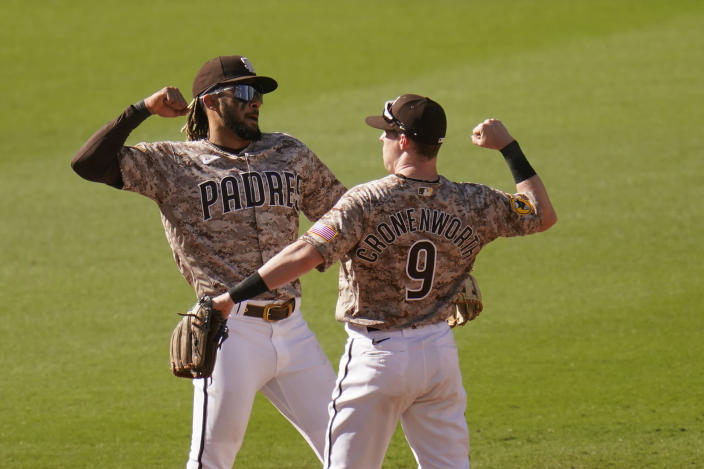 San Diego Padres shortstop Fernando Tatis Jr, left, and second baseman Jake Cronenworth (9) celebrate after they defeated the Los Angeles Dodgers in a baseball game Sunday, April 18, 2021, in San Diego. (AP Photo/Gregory Bull)