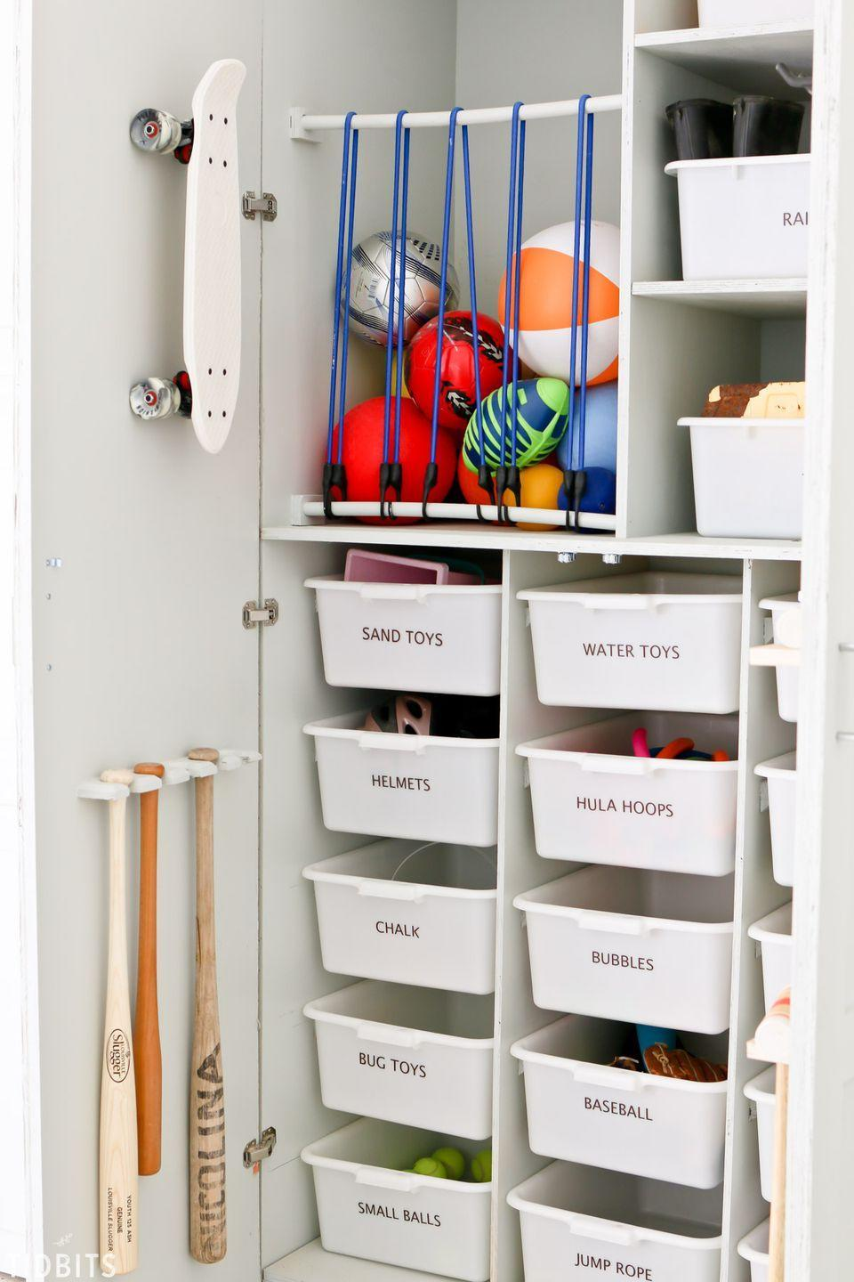 """<p>Take the sports equipment outside in its very own cabinet with bins for balls, hooks for bats and rackets, and drawers for chalk, knee pads, and water toys.</p><p><strong>See more at <a href=""""https://www.tidbits-cami.com/garage-toy-storage/"""" rel=""""nofollow noopener"""" target=""""_blank"""" data-ylk=""""slk:Tidbits-Cami"""" class=""""link rapid-noclick-resp"""">Tidbits-Cami</a>.</strong></p><p><strong><a class=""""link rapid-noclick-resp"""" href=""""https://www.amazon.com/s?k=plastic+storage+bins&ref=nb_sb_noss_2&tag=syn-yahoo-20&ascsubtag=%5Bartid%7C10063.g.36014277%5Bsrc%7Cyahoo-us"""" rel=""""nofollow noopener"""" target=""""_blank"""" data-ylk=""""slk:SHOP PLASTIC STORAGE BINS"""">SHOP PLASTIC STORAGE BINS</a><br></strong></p>"""