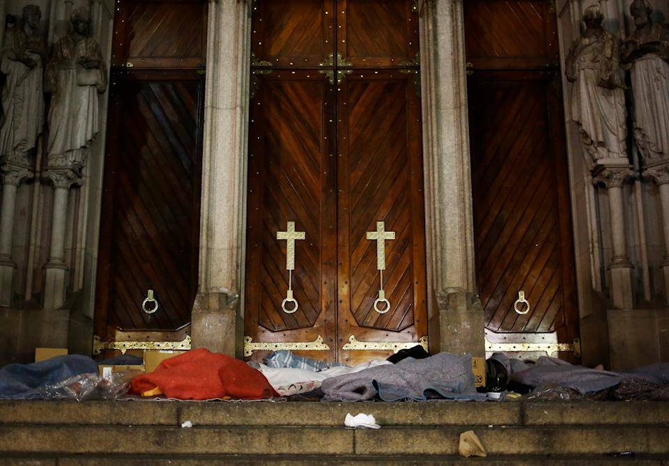Homeless people covered in blankets sleep at the entrance of Se Cathedral, on a cold night in Sao Paulo, Brazil, June 12, 2016. REUTERS/Nacho Doce