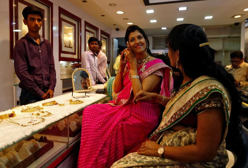 A woman tries a gold earring at a jewellery showroom during Dhanteras in Mumbai