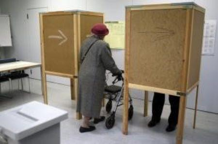 A woman enters a voting booth during regional elections in Vienna, Austria, October 11, 2015. REUTERS/Heinz-Peter Bader