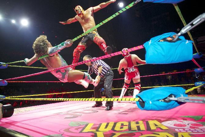 In this Wednesday, Feb. 12, 2014 photo, wrestler Niebla Roja, top, flies over referee Platainitos, to land on wrestler Cassandro, left, during a performance at Lucha VaVoom's Valentine's show at The Mayan Theatre downtown Los Angeles. At right, wrestler, Dr. Maldad. The esoteric hybrid of American burlesque and Mexican wrestling is an outrageous hit. (AP Photo/Damian Dovarganes)