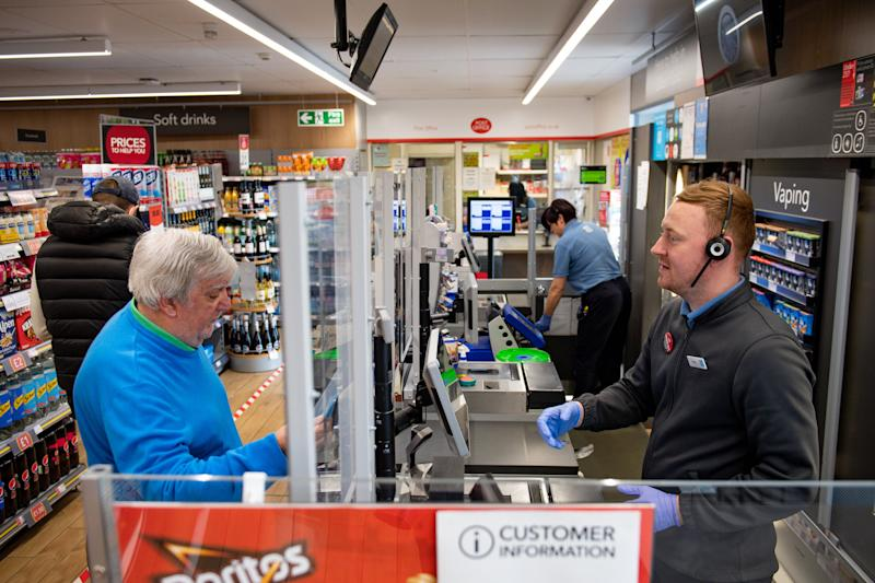 A clear screen divides employees and customers in store at a Co-op shop in Bromsgrove, Worcestershire. (Photo by Jacob King/PA Images via Getty Images)