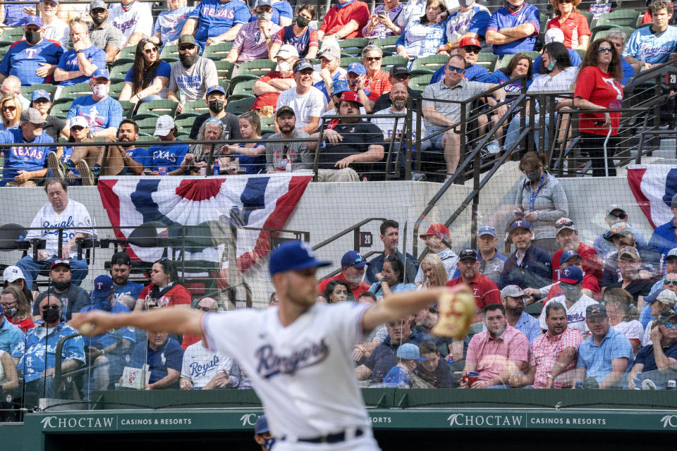 Texas Rangers fans watch relief pitcher Kyle Cody work against the Toronto Blue Jays during the seventh inning of a baseball game Monday, April 5, 2021, in Arlington, Texas. (AP Photo/Jeffrey McWhorter)