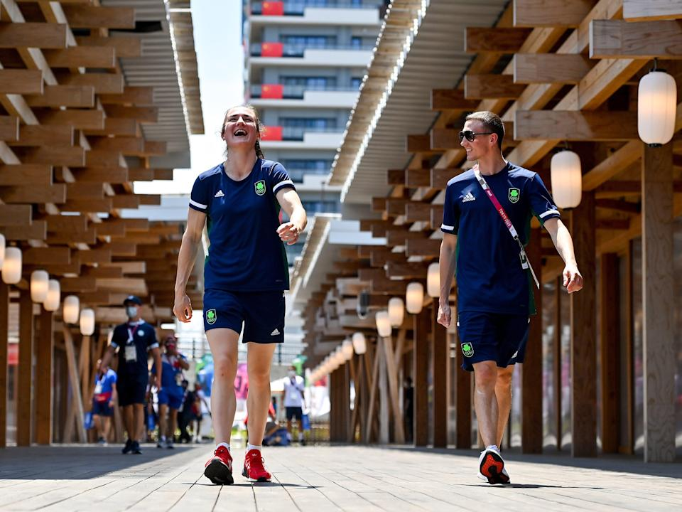Two athletes walk through the olympic village