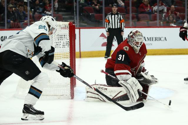Arizona Coyotes goaltender Adin Hill (31) flips the puck away after a shot from San Jose Sharks left wing Marcus Sorensen (20) during the first period of an NHL hockey game Tuesday, Jan. 14, 2020, in Glendale, Ariz. (AP Photo/Ross D. Franklin)