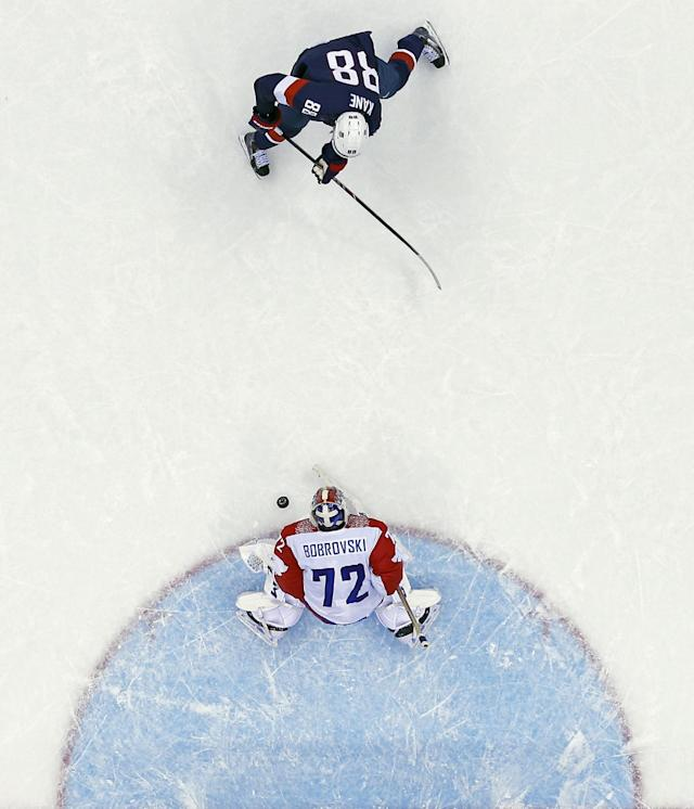 Russia goaltender Sergei Bobrovski stops a break away from USA forward Patrick Kane in overtime of a men's ice hockey game at the 2014 Winter Olympics, Saturday, Feb. 15, 2014, in Sochi, Russia. (AP Photo/Julio Cortez )
