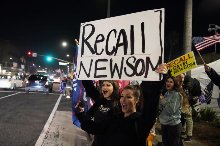 FILE - In this Nov. 21, 2020, file photo, demonstrators shout slogans while carrying a sign calling for a recall on Gov. Gavin Newsom during a protest against a stay-at-home order amid the COVID-19 pandemic in Huntington Beach, Calif. Newsom is facing the possibility that he could be removed by voters in a recall election later this year, in the midst of his four-year term. (AP Photo/Marcio Jose Sanchez, File)