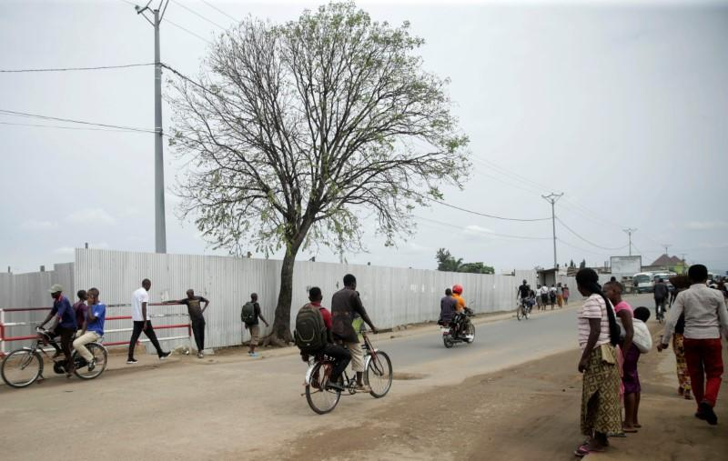 People walk around the area secured with iron-sheet fence where a mass grave was identified, in Kamenge neighbourhood, Bujumbura