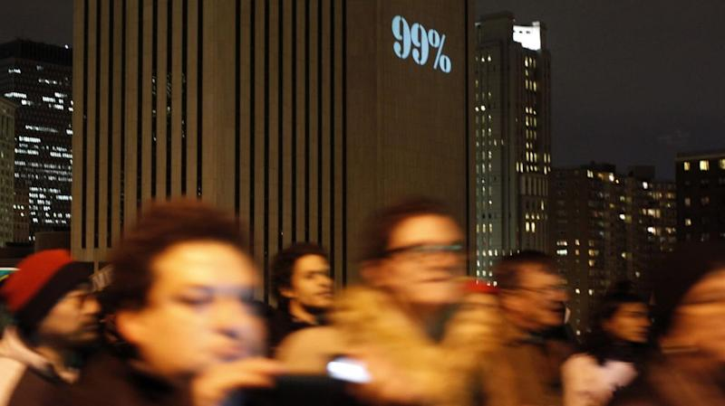 Occupy Wall Street protesters march over the Brooklyn Bridge, with 99% projected onto the Verizon building