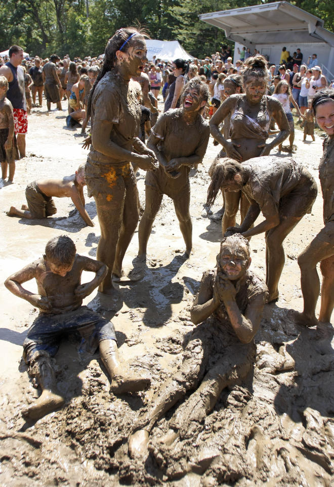 "Kids play in a giant lake of mud at the 25th annual ""Mud Day"" July 10, 2012 in Westland, Michigan. The event, which features a 75' by 150' pit filled with 20,000 gallons of water and 200 tons of topsoil, draws about a thousand children each year. (photo by Bill Pugliano/Getty Images)"