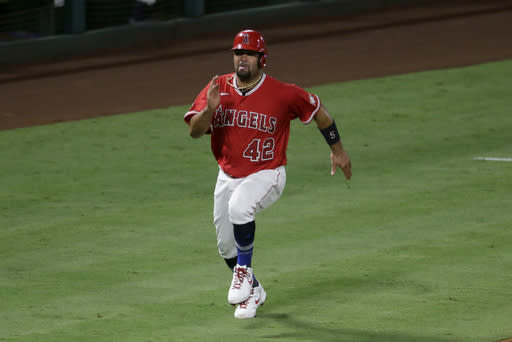 Los Angeles Angels' Albert Pujols races home to score on a single by Justin Upton against the Seattle Mariners during the sixth inning of a baseball game in Anaheim, Calif., Friday, Aug. 28, 2020. (AP Photo/Alex Gallardo)