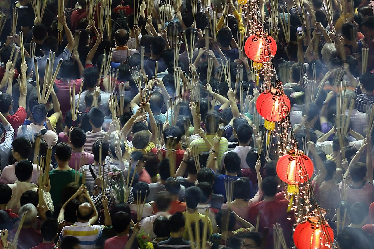 SINGAPORE - FEBRUARY 10:  Worshippers gather at Kwan Im Thong Hood Cho Temple on Lunar New Year to offer prayers and place joss sticks on February 10, 2013 in Singapore. Thousands gathered today to celebrate the Chinese New Year and welcome the the Year of the Snake, with new year's day falling on February 10. Chinese new Year is the most important festival in the Chinese calendar and is celebrated in Singapore and many other Southeast Asian countries with significant Chinese Populations.  (Photo by Suhaimi Abdullah/Getty Images)
