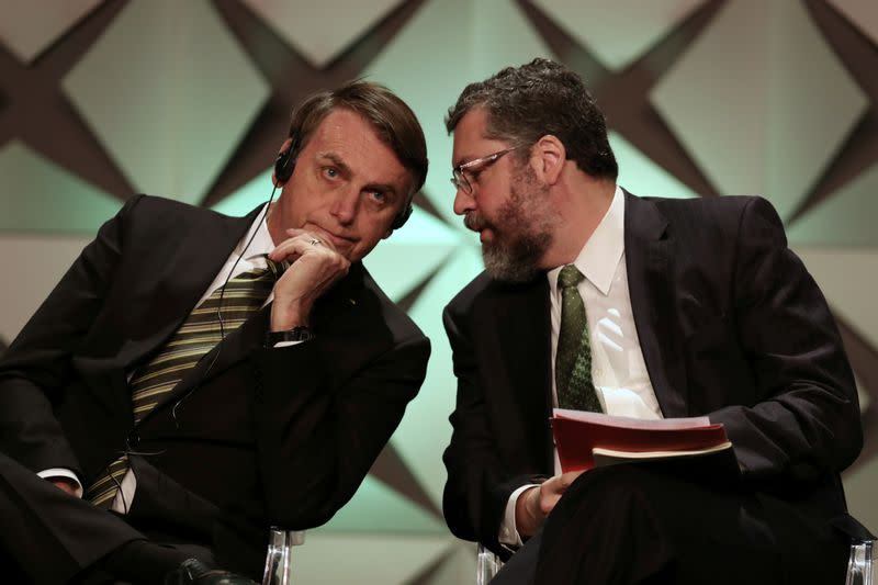 FILE PHOTO: Brazil's President Jair Bolsonaro talks to Minister of Foreign Affairs Ernesto Araujo during the Brazil Investment Forum in Sao Paulo