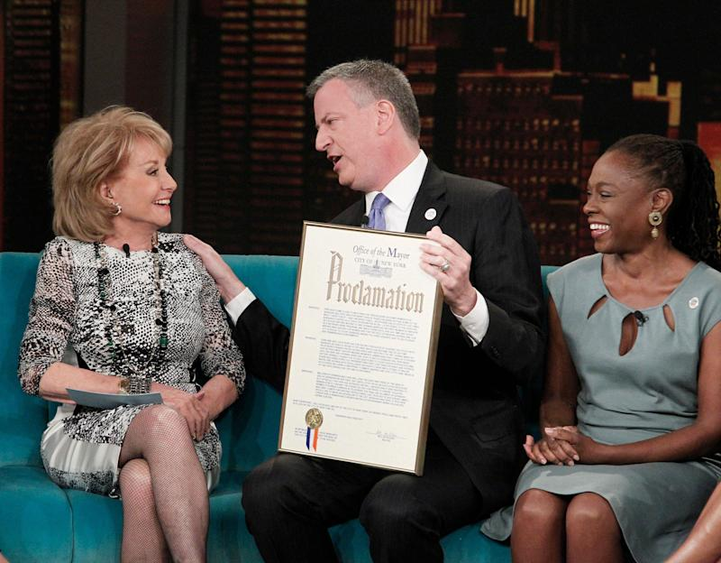 """This image released by ABC shows host Barbara Walters, left, with New York City Mayor Bill de Blasio and his wife Chirlane McCray on ABC's """"The View,"""" Monday, April 21, 2014 in New York. De Blasio is proclaiming May 16 as """"Barbara Walters Day"""" in New York City. Walters is retiring that day after a storied television reporting career that has spanned five decades. (AP Photo/ABC, Lou Rocco)"""