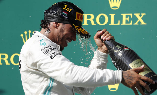 Mercedes driver Lewis Hamilton of Britain celebrates on the podium after winning the Hungarian Formula One Grand Prix at the Hungaroring racetrack in Mogyorod, northeast of Budapest, Hungary, Sunday, Aug. 4, 2019. (AP Photo/Laszlo Balogh)