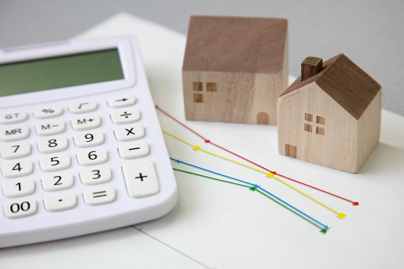 Miniature house and calculator (Photo: key05 via Getty Images)