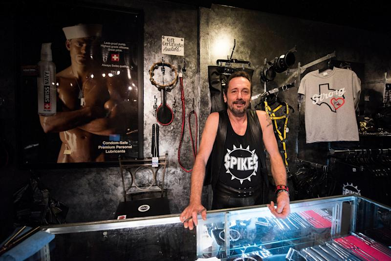 Rod Caldwell, co-owner of Spike's Leather Club in Birmingham, Alabama, stands behind a glass counter in their boutique.  (Damon Dahlen/HuffPost)