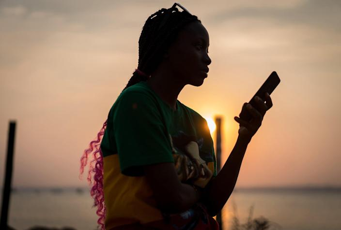Afro american woman sitting on shore using a mobile phone at sunset