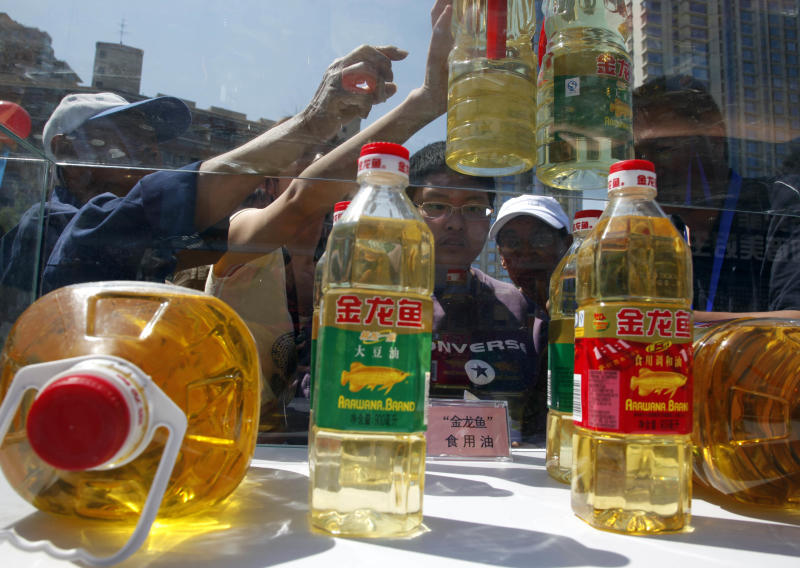 Chinese residents try to tell counterfeit cooking oil products from the real products during an event to promote awareness of economic crimes in Beijing, China, Sunday, May 15, 2011.  The headlines are unrelenting: toxic bean sprouts, filthy oil, drug-tainted pork. For months, Chinese media have been churning out a queasy-making multitude of stories about the dangers lurking in the nation's dinner bowls. (AP Photo/Ng Han Guan)