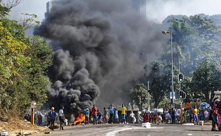 Looters outside a shopping centre alongside a burning barricade in Durban, South Africa. Former president Jacob Zuma's incarceration for contempt of court, sparked off the worst violence South Africa has seen since the nation achieved democracy in 1994. (AP Photo/Andre Swart, File)