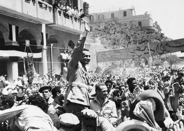 Egyptian leader Gamal Abdel Nasser waves as he moves through Port Said, Egypt, on June 18, 1956, during a ceremony in which Egypt formally took over control of the Suez Canal from Britain.